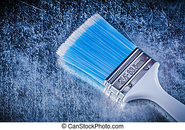 Paintbrush on scratched metallic background construction concept