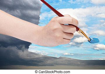 paintbrush paints blue sky on storm clouds
