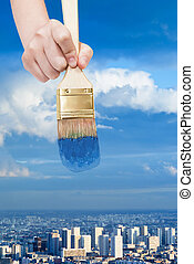 paintbrush paints blue sky over blue city
