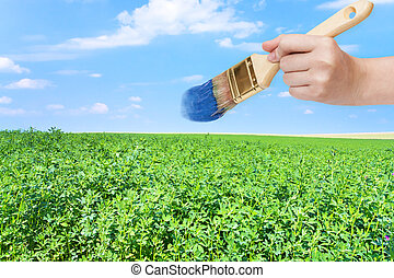paintbrush paints blue sky over green field