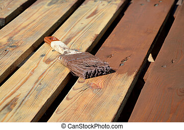 Paintbrush with brown paint on planks