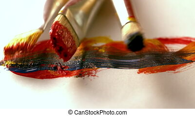 Paintbrushes dropping on page with brushstrokes in slow...