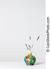Paintbrushes in a colorful ceramic vase