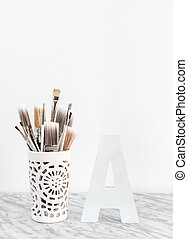 Paintbrushes in a decorative vase and letter A on marble surface