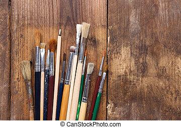Paintbrushes on a wood background