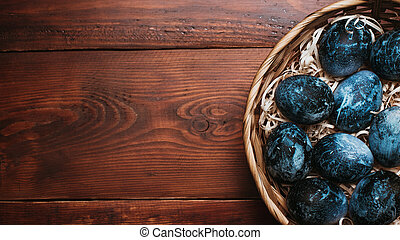 blue Easter eggs in a basket on a wooden background