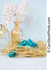 Painted blue Easter quail eggs in the nest, flowers. Easter concept.