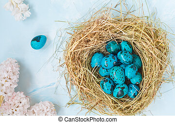 Painted blue Easter quail eggs in the nest, flowers. Top view. Easter concept.