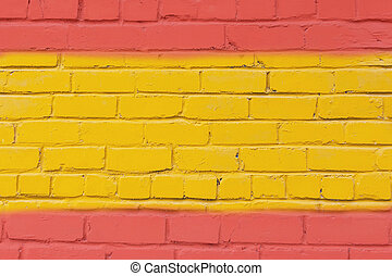 Painted brick wall in the colors of the flag of Spain.