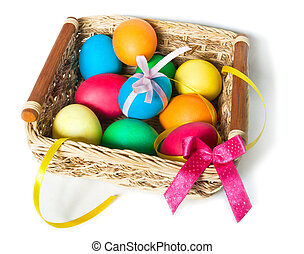 Painted Easter eggs in a basket with ribbons on white background