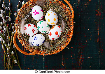 Painted Easter eggs in a wicker basket on wooden table