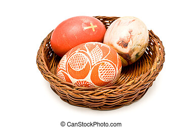 Painted easter eggs in brown basket isolated on white
