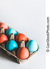 Painted easter eggs in carton box on white background. Trendy blue and red color