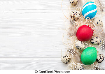 Painted Easter eggs on white wooden background