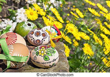 Painted Easter eggs with yellow flowers in the garden