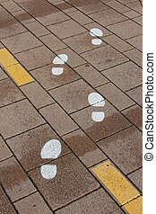 painted footprints on the pavement as a guide