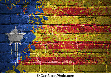 painted national flag of catalonia on a brick wall