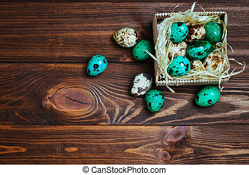 Painted quail eggs in the box over wooden background