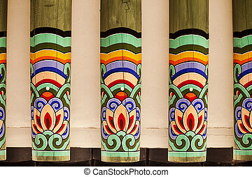 An architectural detail showing a row of painted rafters in a Korean royal palace. Each beam is painted with the same pattern.