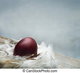 Painted red easter egg in bird feather nest over vintage blue artistic canvas textured background.
