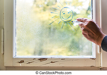 painted sun on a window with water drops