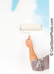 painter arm painting a wall with paint roller