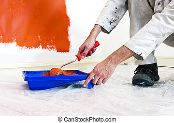 Painter at work - Painter refilling his paint roller whilst ...