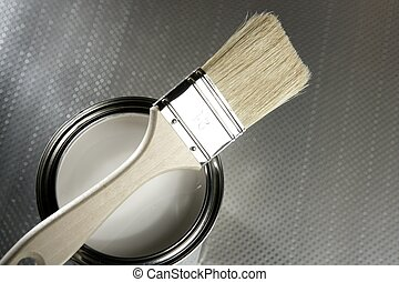 Painter brush and white paint tin macro over silver pattern...