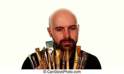 Painter choosing paintbrush among a lot of it, on white background