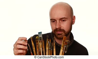 Painter choosing paintbrush among a lot of it, on white background, slow motion