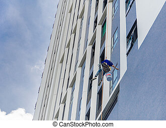 Painter coming down the facade of a building tower rappelling with a rope.