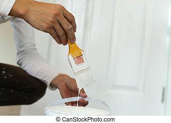 Painter hand holding yellow brush painting