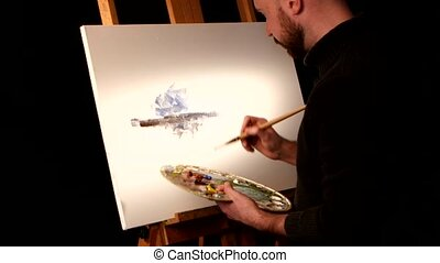Painter holding the palette in his hand continues drawing a new painting with oil paints on easel, black background, back light