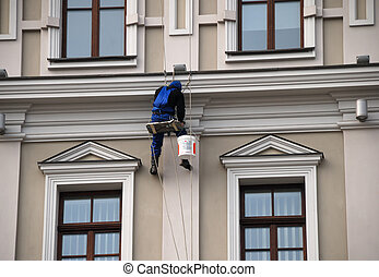 Painter hovers between four windows of mansion - Painter...