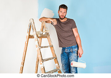 painter in paint splattered shirt painting a wall