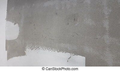 Painter is smoothing wall before painting with trowel, skim...
