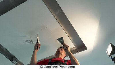 Painter man apply plaster filler on ceiling between niches ...