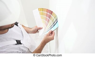painter man at work choice color with swatches samples, wall...