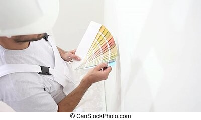 painter man at work choice color with swatches samples, wall painting concept, white copy space background