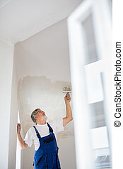 Painter man at work with a paint bucket, wall painting concept
