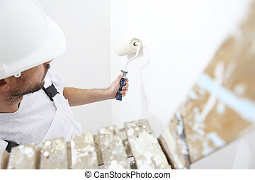 painter man at work with a paint roller, on ladder, wall painting concept