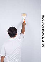 painter man at work with a paint roller on wall