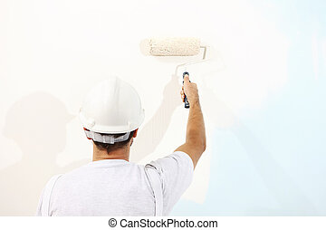 painter man at work with a paint roller, wall painting concept