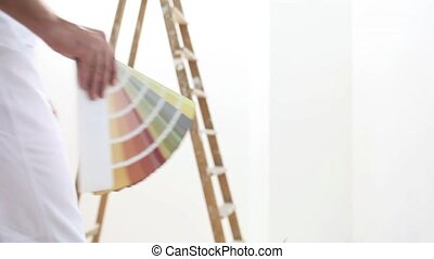 painter man at work with color swatches samples, wall...