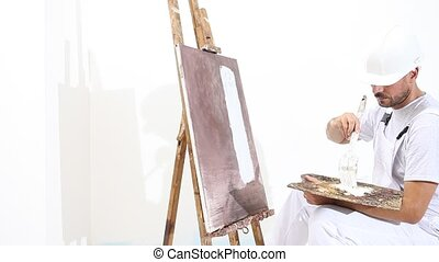 painter man at work with paint brush, easel, canvas and...