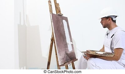 painter man at work with paint roller, easel, canvas and...