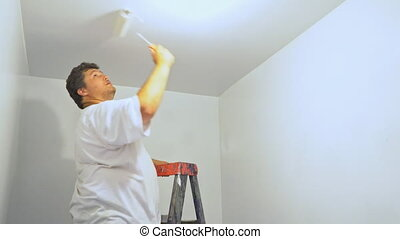 Painter man at work with roller painting ceiling ladder in...