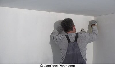 painter man grinds wall. Handyman aligns walls with...