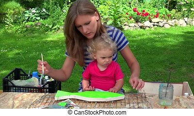 painter mother with her toddler daughter girl paint wooden fish decoration