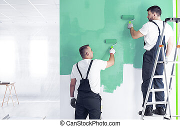 Painter on ladder painting wall on green while redecorating interior